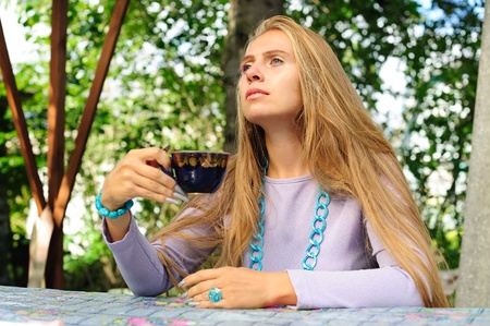 blonde haired: Girl sitting at the table, holding a cup and pondering