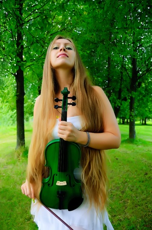 Young girl holding the green violin photo