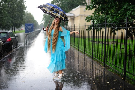 Smiling girl with umbrella under the pouring rain Stock Photo - 10712302