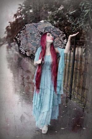 sotto la pioggia: Ragazza sorridente con ombrello sotto la pioggia, foto in stile retrò Archivio Fotografico