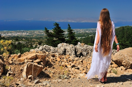 Beautiful long-haired girl looking afar from the mountain Standard-Bild