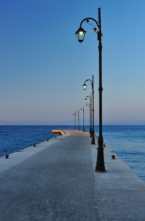 aegean sea: Pier with street lamps in the evening Stock Photo