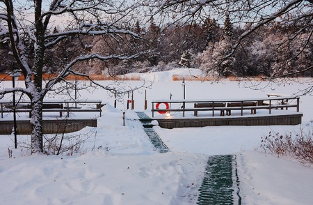 finland sauna: Jetty near an ice hole with a heated path going from the sauna Stock Photo