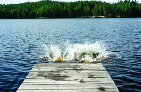 Two splashes left by people who dived from the pier on the lake