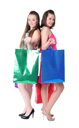 Pretty young girls with colorful shopping bags standing back to back photo