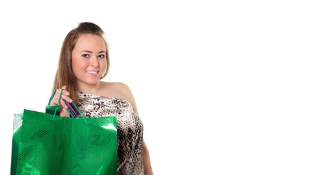 Portrait of a beautiful smiling girl holding bright green shopping bag with purchases with copyspace for text photo