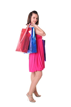 Beautiful young girl in pink dress holding colorful shopping bags with purchases  photo