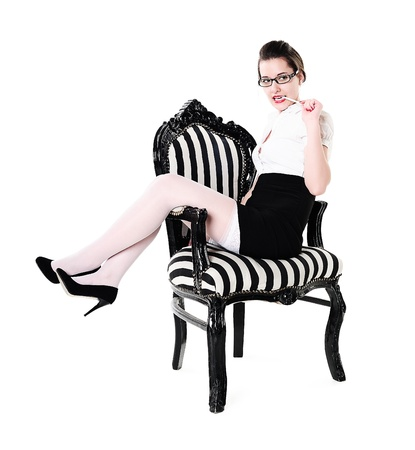 Attractive young girl sitting in retro black-and-white chair and gnawing a pencil photo