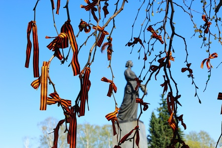 SAINT-PETERSBURG, RUSSIA - MAY 9: St. George's Ribbons (symbols of victory in World War II) on tree branches and the Statue of Mother Homeland on Piskaryovskoye Memorial Cemetery on May 9, 2011 in Saint-Petersburg, Russia