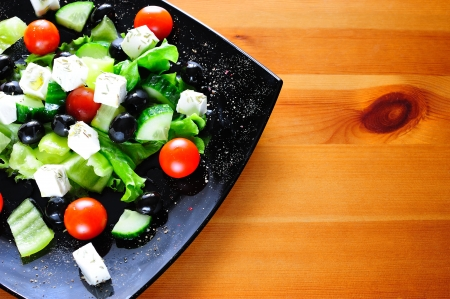 Tasty Greek salad dressed with olive oil and rosemary on wooden table with copyspace for text