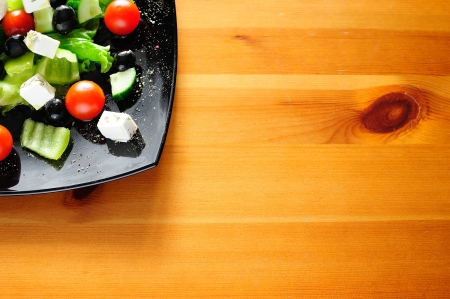 Delicious Greek salad on wooden table with copyspace for text photo