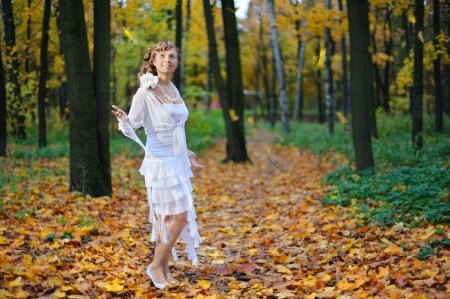 Full-length portrait of a bride in an autumn park photo