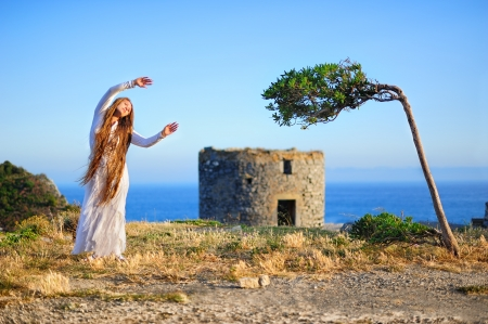 Landscape with a beautiful girl and an olive tree photo