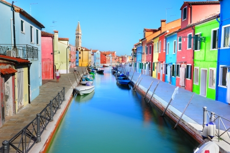 Burano island colorful scenery with bright colorful houses along the canal embankment (Venice, Italy)