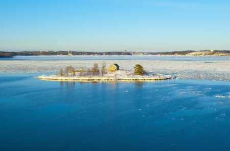 Snowy island in the middle of the ice drift in the Baltic sea in Finland photo