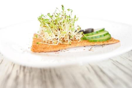 Les graines germ�es de luzerne servis avec des concombres, des olives et une tranche de pain de seigle