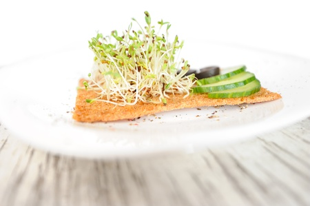Sprouted seeds of alfalfa served with cucumbers, olives and a slice of rye bread