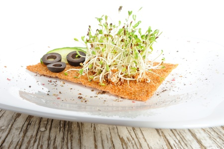 medicago: Healthy meal of coached seeds of alfalfa (Medicago) served with cucumbers, olives and a slice of rye bread