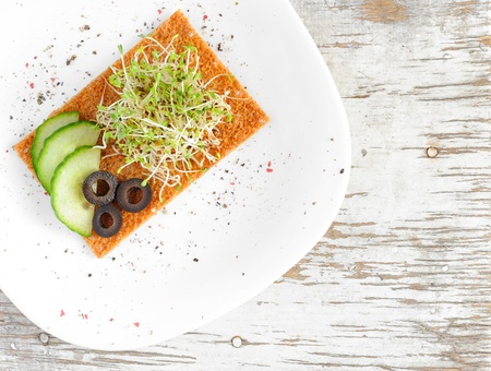 medicago: Healthy eco food of sprouted grains of alfalfa served with cucumbers, olives, a slice of rye bread and spices Stock Photo