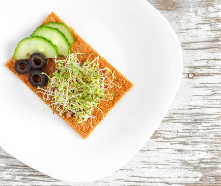 medicago: Healthy meal of sprouted grains of alfalfa (Medicago) served with cucumbers, olives and a slice of rye bread