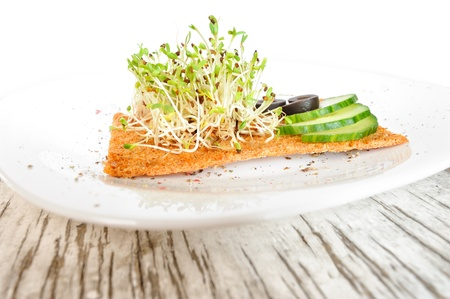 medicago: Sprouted grains of alfalfa served on a white plate with cucumbers, olives and a slice of bread