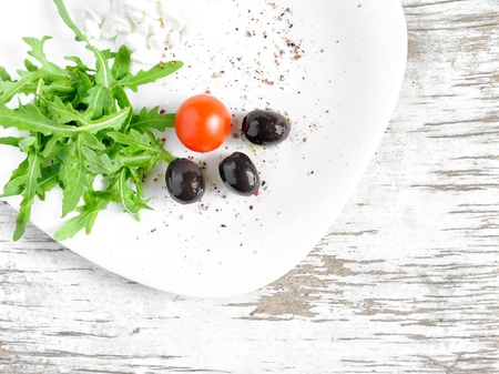Salad made of rucola (or arugula), cherry tomato, cottage cheese, olives and spices served on a white plate photo