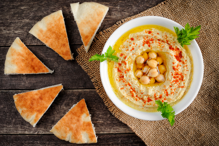 Fresh bowl of homemade hummus with chickpeas, olive oil and parsley. Served with pita bread