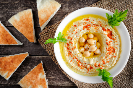 Homemade hummus with pita bread, olive oil and parsley. Served with fresh pita bread