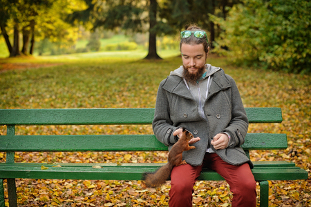 animal in the wild: Bearded man feeds a squirrel in the autumn park