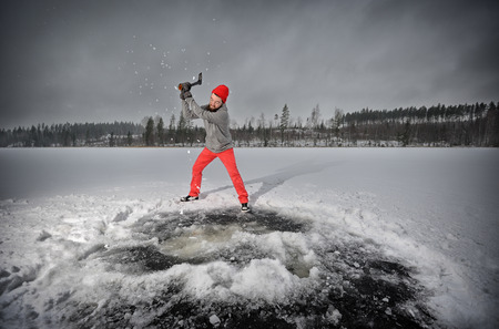 ax man: Bearded man with an ax chops ice at the lake
