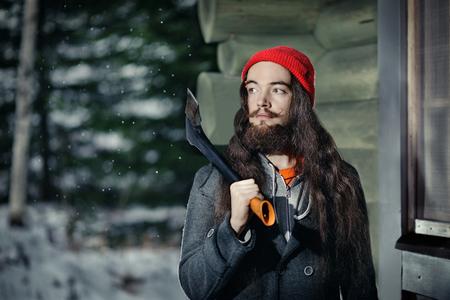 winter fashion: Bearded lumberjack near his hut in a winter forest