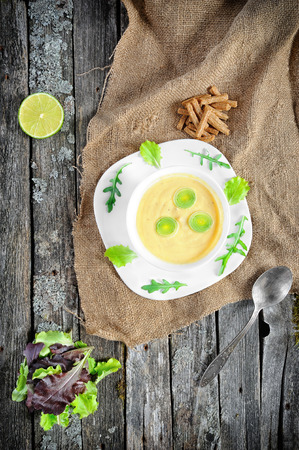 celeriac: Hot cream of celeriac soup with croutons and leek on vintage wooden background Stock Photo