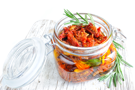 sundried: Sun-dried tomatoes with rosemary, olive oil and garlic in a glass jar Stock Photo
