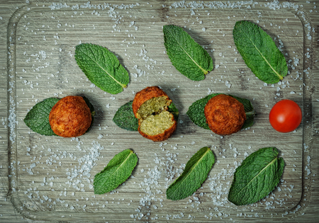 lebanese food: Falafel balls served on a wooden board with fresh mint leaves