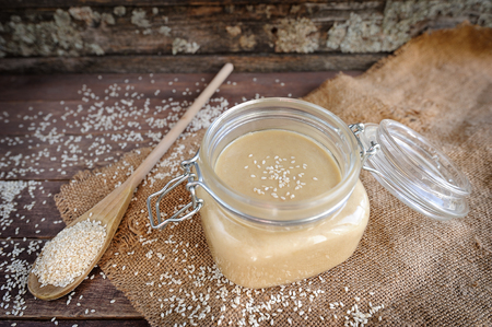 Fresh homemade Tahini (sesame paste) in a glass jar, selective focus
