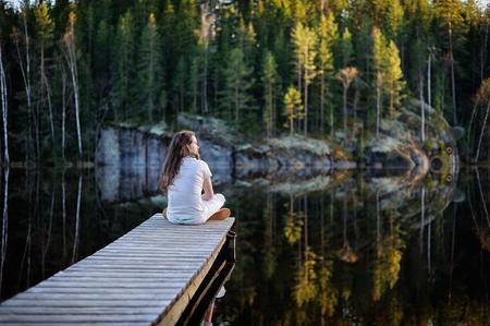 Traveler man zitten en mediteren op een ponton door een meer op de ochtend
