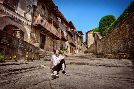 village man: Young tourist resting on an old street in medieval town Rupit, Catalonia, Spain