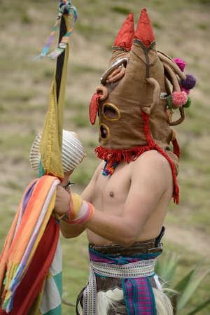 Man in mask celebrating solstice holiday in Latin America.