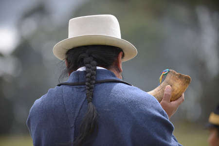 quechua indian: Indian man is playing the horn.