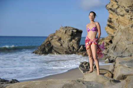 ocean and sea: Woman in swimming suit and pareo on the rocky ocean beach. Stock Photo