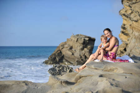 pareo: Woman in swimming suit with child on her hands on the rocky beach.