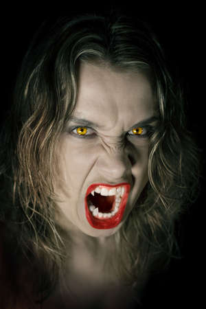 Young and hungry vampire on black background