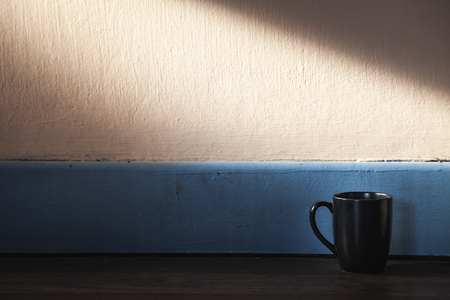 Coffee cup black color with sunlight on Plank