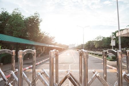 Aluminum fence Luster It is used for shutting down entrances and exits in places where no cars are allowed. and have road has a long straight is background.
