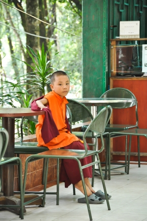 resturant: GUNGTOK, SIKKIM, INDIA - OCT 24, 2011: An Unidentified lama sits in the resturant on the walkway to Do Drul Chorten Monestery in Gungtok, Sikkim, India