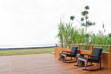 Le fauteuil en bois sur le balcon avec un arbre
