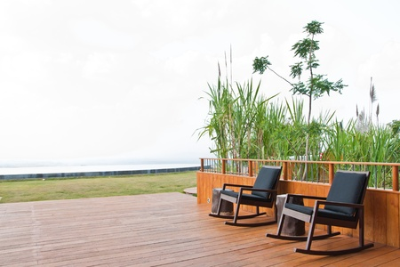 The wooden armchair on the balcony with tree