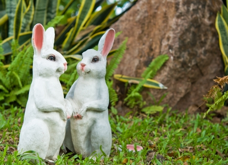 The two rabbit dolls in the garden as background photo
