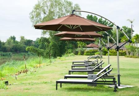 The umbrella and seat in the garden near river photo