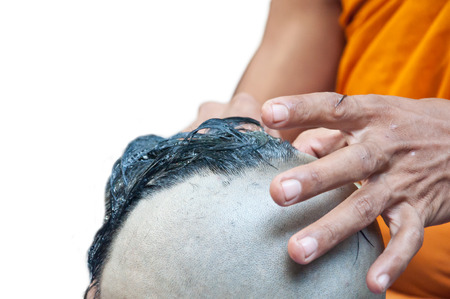 ordain: A man is shaved his hair preparing to be ordained Stock Photo